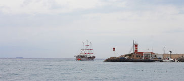 Sail ship moving away from the shore Stock Photos