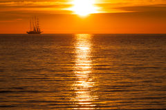 Sail ship silhouette at sea and sun Stock Images