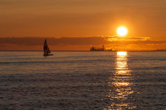Sail and ship at sunset on Pacific ocean Royalty Free Stock Photos