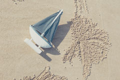 Sail Ship Toy Model in the Beach Sand Stock Photo