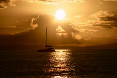 Sail at sunset. A catamaran on the water at sunset stock image