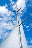 Sail yacht mast. With white sail against blue sky Royalty Free Stock Image