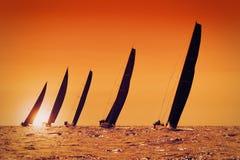 Sail yachts at sunset. Sailing yachts at sunset on the sea Stock Images