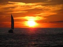 Sailboar en la puesta del sol Fotos de archivo