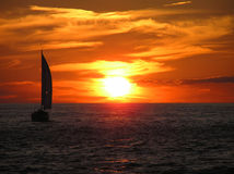 Sailboar Into the Sunset. A boat sails into the sunset stock photos