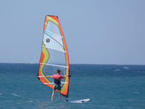 Sailboard sportsman. A water sportsman enjoying an outing on a sailboard Stock Photos