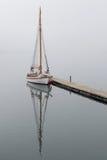 Sailboat καθρέφτες σε ένα ομιχλώδες Holandsfjord Στοκ Εικόνα