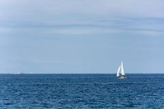 Sailboat ολισθήσεις πέρα από το φωτεινό ωκεανό Στοκ φωτογραφίες με δικαίωμα ελεύθερης χρήσης