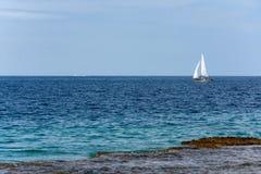 Sailboat ολισθήσεις πέρα από το φωτεινό ωκεανό Στοκ Εικόνες