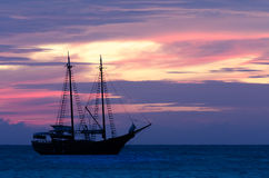 Sailboat πειρατών στη θάλασσα που πλοηγεί προς το ηλιοβασίλεμα Στοκ Εικόνες