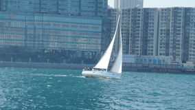 Sailboat που πλέει με τη θάλασσα κοντά στην παραλία πόλεων σε μια ηλιόλουστη ημέρα Στοκ Εικόνα