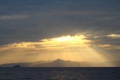 Sailboat που τρέχει κάτω από το φως του ήλιου που διαρρέει μέσω των σύννεφων Στοκ Εικόνες