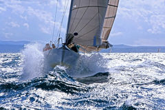 Sailboat σπάσιμο μέσω του καταβρέχοντας κύματος Στοκ εικόνα με δικαίωμα ελεύθερης χρήσης