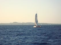 Sailboat στο ηλιοβασίλεμα Θάλασσα, βουνά και ηλιοβασίλεμα στοκ εικόνες
