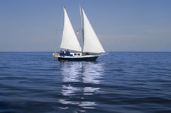 Sailboat. On still blue water Royalty Free Stock Photos