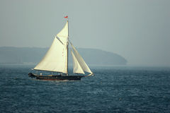 Sailboat. Leaving a misty harbor royalty free stock photos