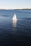 Sailboat. A small sailboat on the open blue sea Stock Photo