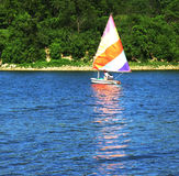 Sailboat. Man sailing on boat on lake stock image