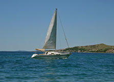 Sailboat on adriatic sea. One small white sailboat sailing at blue Adriatic Sea - Croatia - Dalmatia. Horizontal color photo Royalty Free Stock Image
