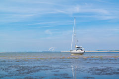 Sailboat aground on sandflat at low tide near Rotterdam, Netherl Royalty Free Stock Image