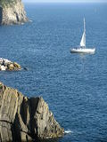 Sailboat along a Rocky Coast. A sailboat sails along the coast of Cinque Terre, Italy Royalty Free Stock Image