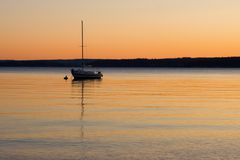Sailboat Silhouette at Sunset. A sailboat anchored on calm waters at sunset Stock Photography