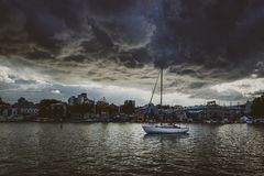 Ominous Clouds Over Isolated Boat. Sailboat anchored in False Creek on a dark, cloudy evening at blue hour, Vancouver, British Columbia stock photo