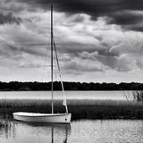 Sailboat anchored on lake during stormy day. In monochrome image Royalty Free Stock Photography