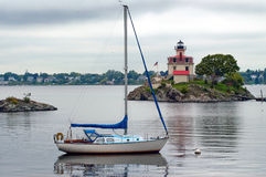 Sailboat Anchored Near Pomham Rock Lighthouse in Rhode Island Royalty Free Stock Images