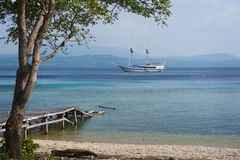 Sailboat Anchored Off of an Indonesian Island Royalty Free Stock Images