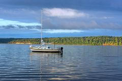 Sailboat anchored upper left. An anchored sailboat floating on calm waters Stock Photo