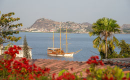 Sailboat approaching a shore on a sunny afternoon Stock Photo
