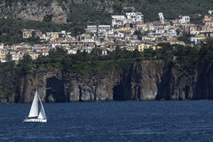 Sailboat approaching Sorrento, Italy. Sailboat approaching Sorrento along the Amalfi Coast, Italy. The city is perched on the top of volcanic cliffs that form Royalty Free Stock Image