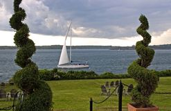 Sailboat and approaching storm. A view across an open lawn at a sailboat on Narragansett Bay in Newport, Rhode Island with dramatic storm clouds approaching Royalty Free Stock Image