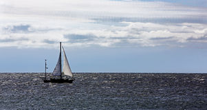 Sailboat on the Atlantic Ocean under a cloudy sky. Royalty Free Stock Photos