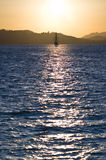 Sailboat bathed in dawn sunlight Stock Photography