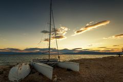 Sailboat on the beach at sunset. Stock Images