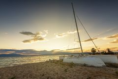 Sailboat on the beach at sunset Stock Images