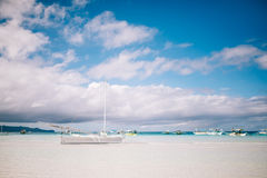Sailboat on the beach with white sand Stock Images