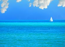 Sailboat on Beautiful Sea. Pretty white sailboat on calm blue sea under cloudy sky Royalty Free Stock Images