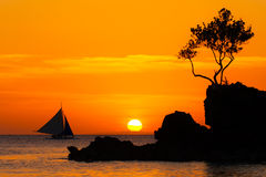 Sailboat at beautiful sunset above the tropical sea. Silhouette Stock Photography