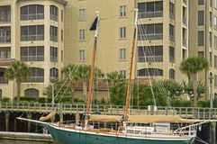Sailboat Berthed at a Condominium. Large sailboat anchored alongside a condominum royalty free stock photography