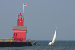 Sailboat and Big Red lighthouse royalty free stock photography