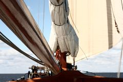 Sailboat with large sail and mast on the sea Stock Photography