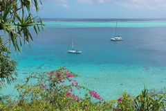 Sailboat in blue lagoon with tropical vegetation Royalty Free Stock Images