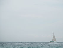 Sailboat in blue sea with clouds sky background in Thailand. Relaxing moments in summer seasons travel. Stock Images