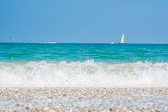 Sailboat with blue sky, turquoise sea and shore full of pebbles Stock Photo