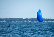 Sailboat with blue spinnaker on lake. Michigan with coastline background Stock Photo