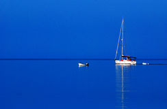 Sailboat on blue water. A view of a sailboat sailing on calm, blue water Stock Photos