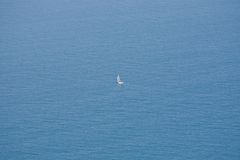 Sailboat and boundless ocean. Lonely sailing yacht on the background of the boundless ocean Stock Photos